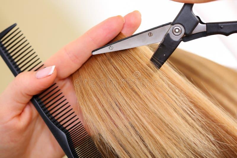 拿着梳子和热的热量剪刀的女性手 免版税库存图片