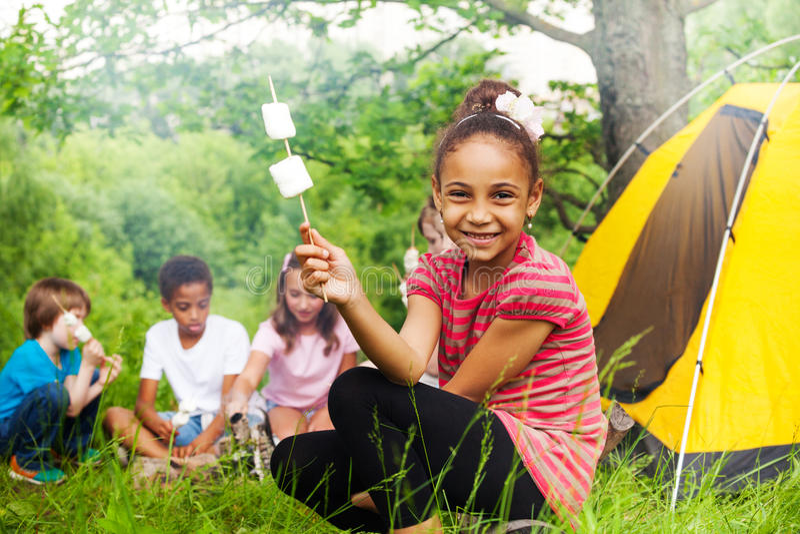 拿着棍子用蛋白软糖的愉快的非洲女孩 库存图片