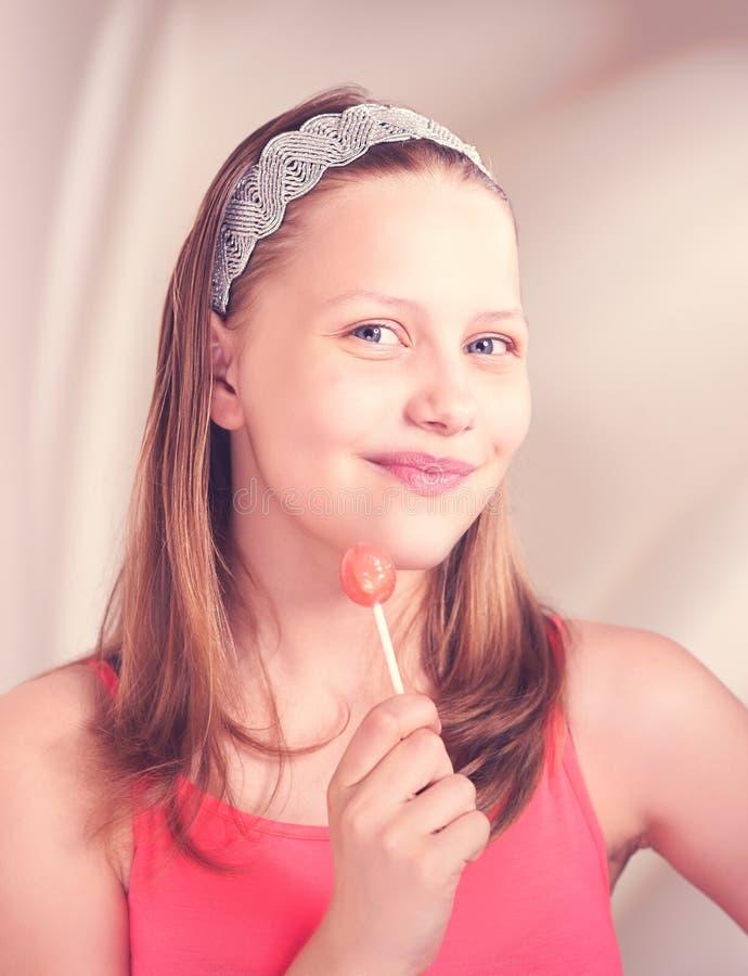 拿着棒棒糖的愉快的青少年的女孩 免版税图库摄影