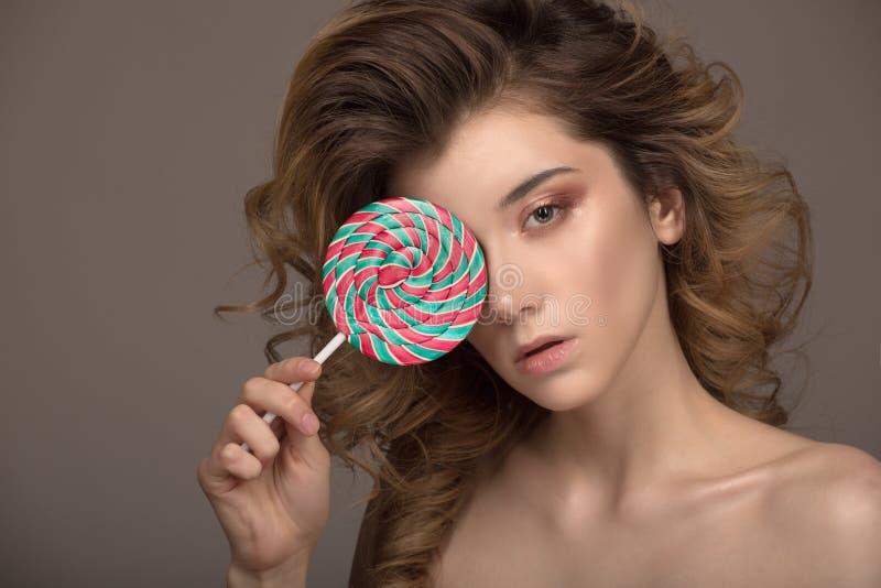 拿着棒棒糖的时尚妇女 美丽的卷发画象  免版税库存图片