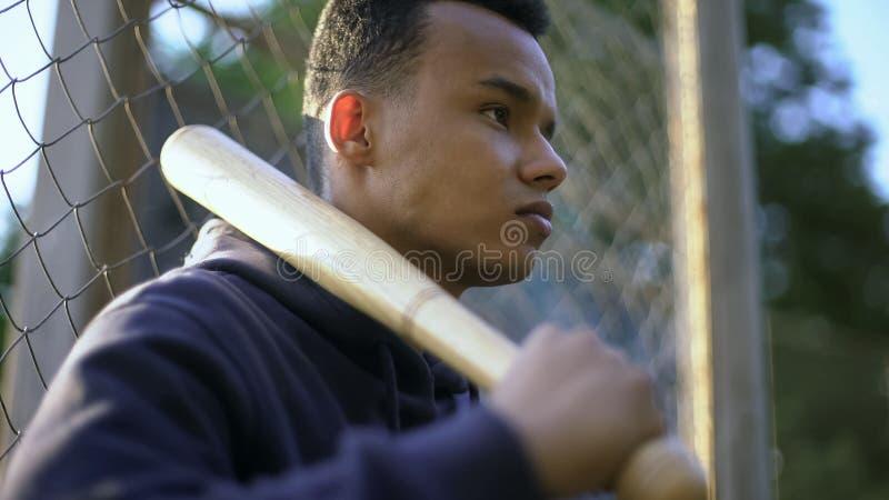 拿着棒球棒,青少年组的十几岁的男孩在少数民族居住区,少年犯罪 库存照片