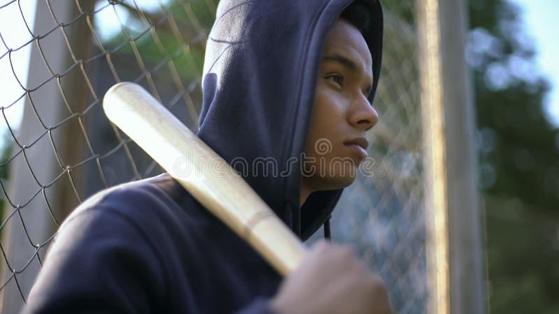 拿着棒球棒,青少年组的美国黑人的少年在少数民族居住区,特写镜头 库存照片
