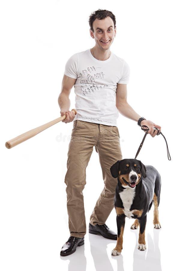 拿着棒,与狗的年轻白种人人 免版税库存图片