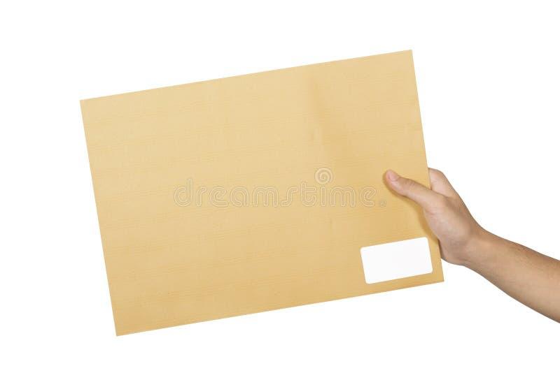 拿着棕色信封的男性手 免版税图库摄影
