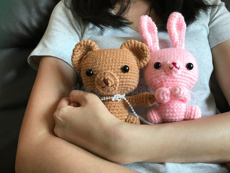 拿着棕色玩具熊ans桃红色兔宝宝钩针编织玩偶的女孩 库存照片