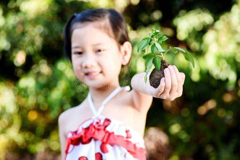 拿着植物幼木的孩子 免版税库存图片