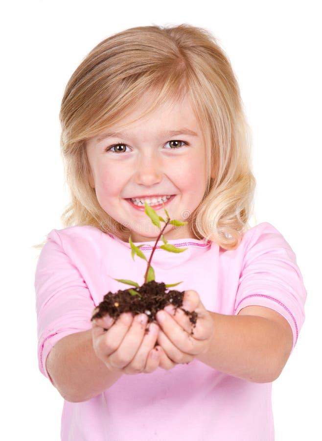 拿着植物的孩子 免版税库存图片