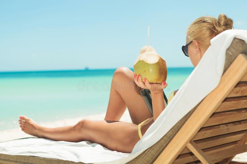 拿着椰子和读在海滩的女孩,当躺下时 免版税库存图片
