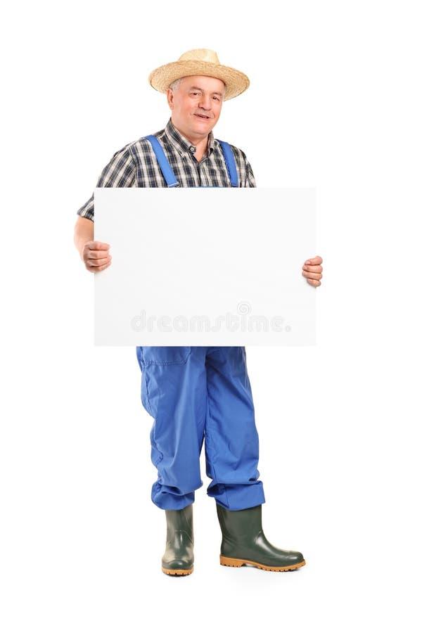 拿着横幅的成熟微笑的农夫 免版税库存图片