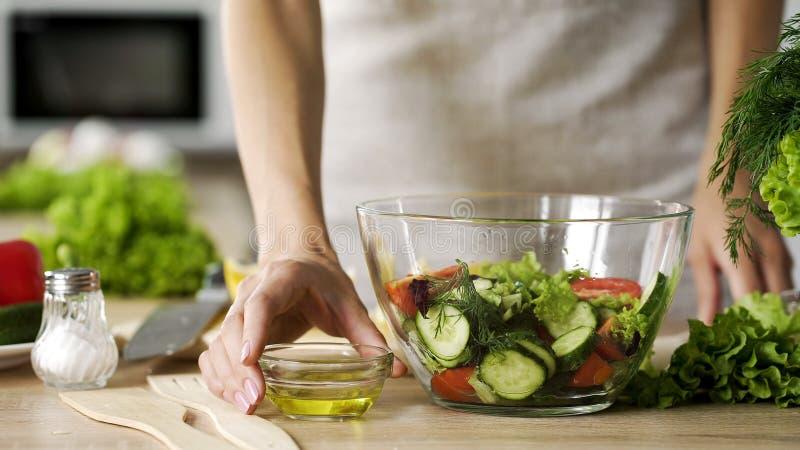 拿着橄榄油的年轻妻子穿戴晒干的新鲜的沙拉碗,节食 图库摄影