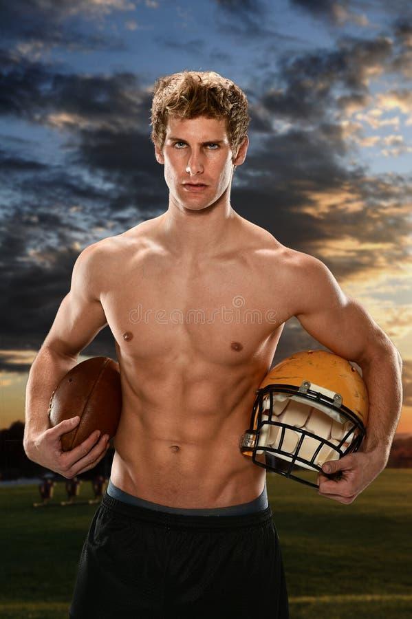 拿着橄榄球和盔甲的年轻人 库存图片