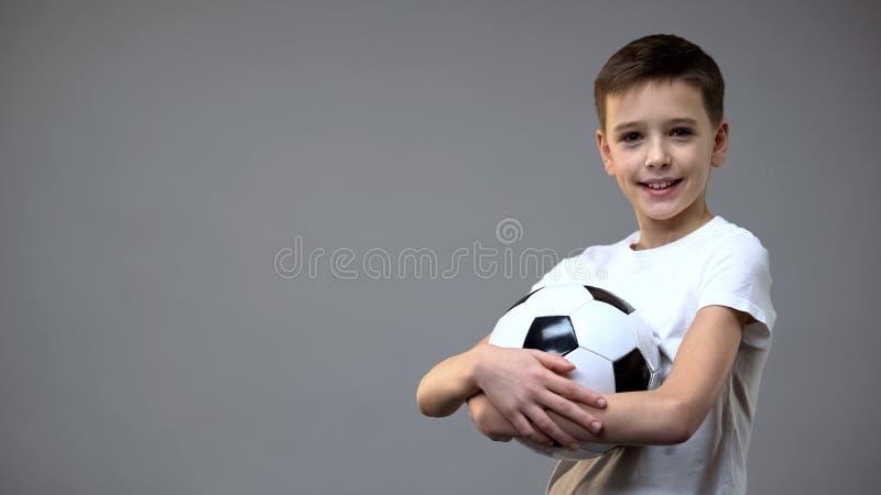 拿着橄榄球球和看对照相机,活跃休闲爱好的男小学生 库存图片