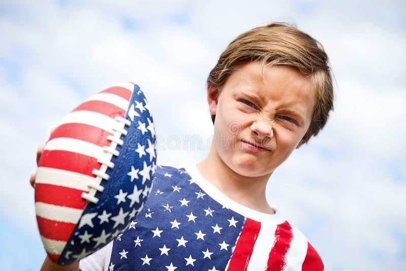 拿着橄榄球球的小美国男孩皱眉 库存图片