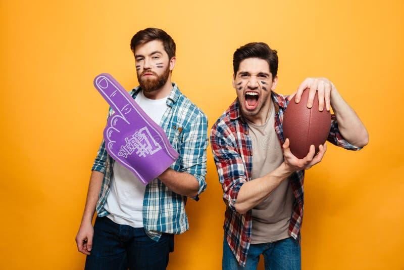 拿着橄榄球球的画象两个快乐的年轻人的 库存照片