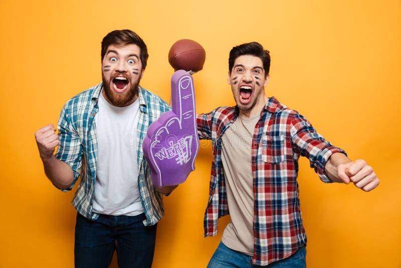 拿着橄榄球球的画象两个快乐的年轻人的 免版税库存照片