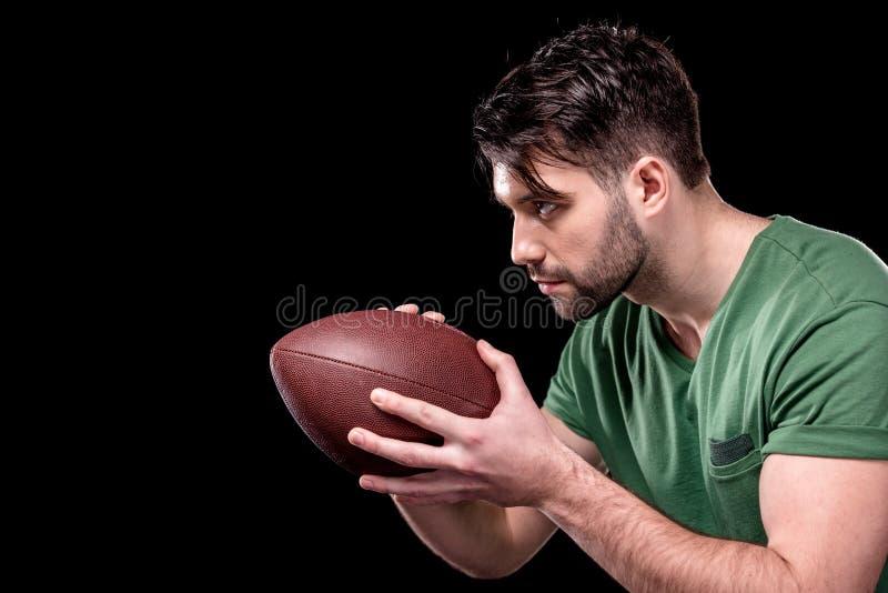 拿着橄榄球球的被集中的人侧视图  库存照片