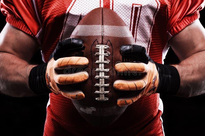 拿着橄榄球球的运动员 图库摄影
