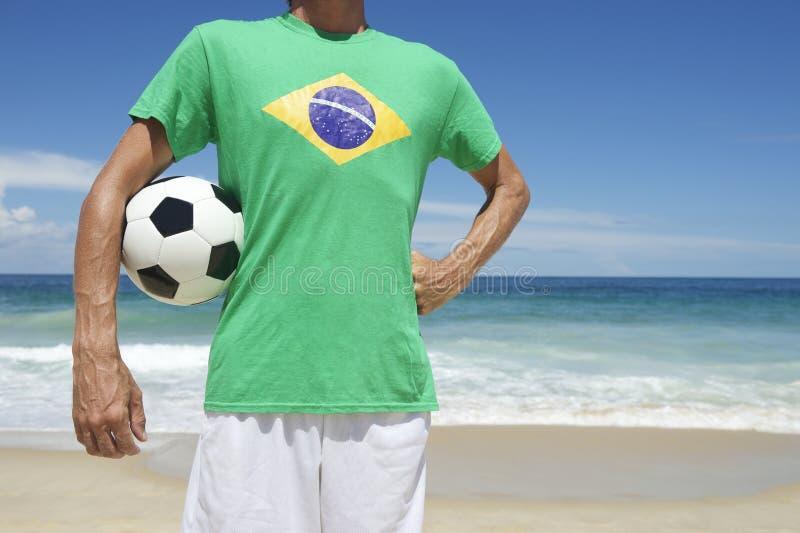 拿着橄榄球巴西海滩的巴西足球运动员 图库摄影