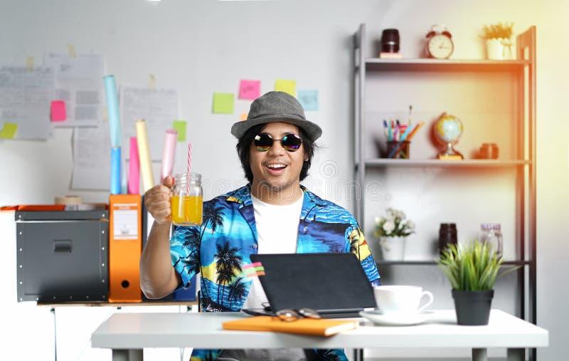拿着橙汁的时髦的年轻人,当研究夏天v时 免版税库存图片