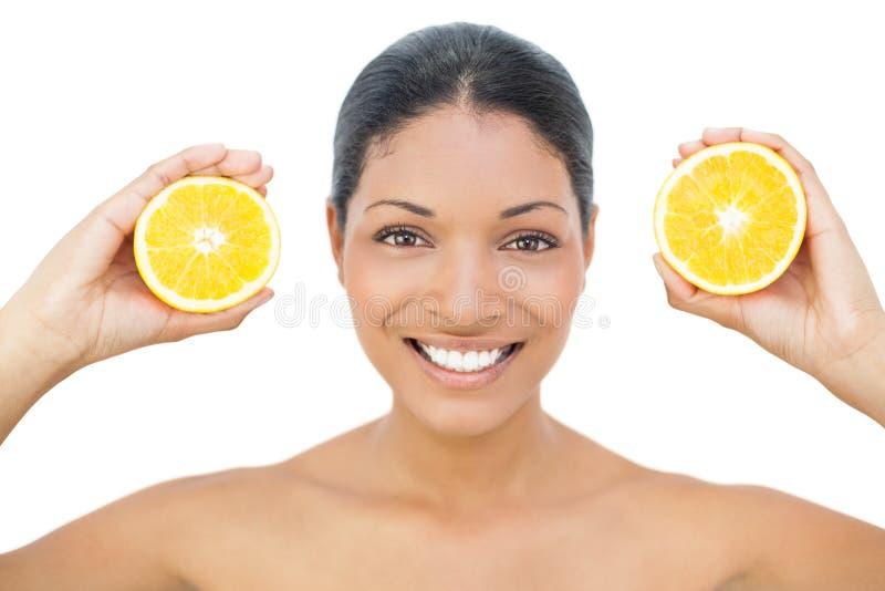 拿着橙色切片的微笑的黑发模型 库存图片