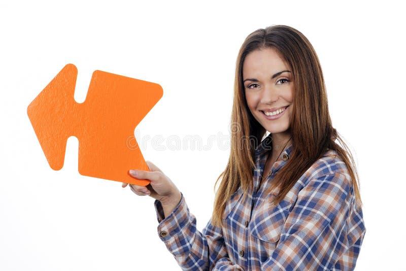 拿着橙色箭头的妇女 库存照片