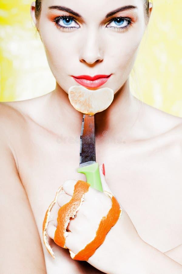 拿着橙色蜜桔果子切片的妇女画象 库存照片