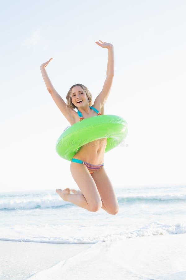 拿着橡胶环的快乐的少妇,当跳跃在海滩时 免版税库存图片