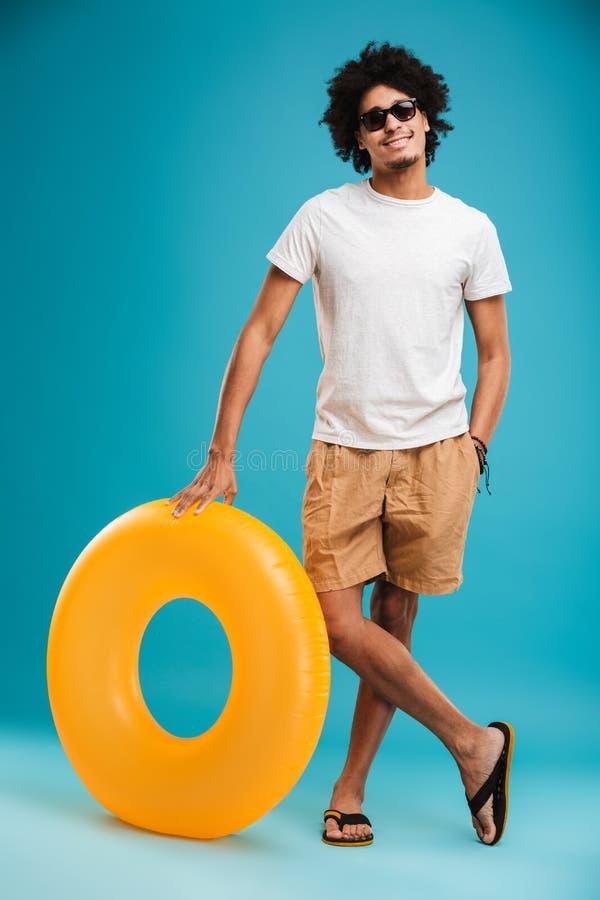拿着橡胶环的英俊的年轻非洲卷曲人 库存图片