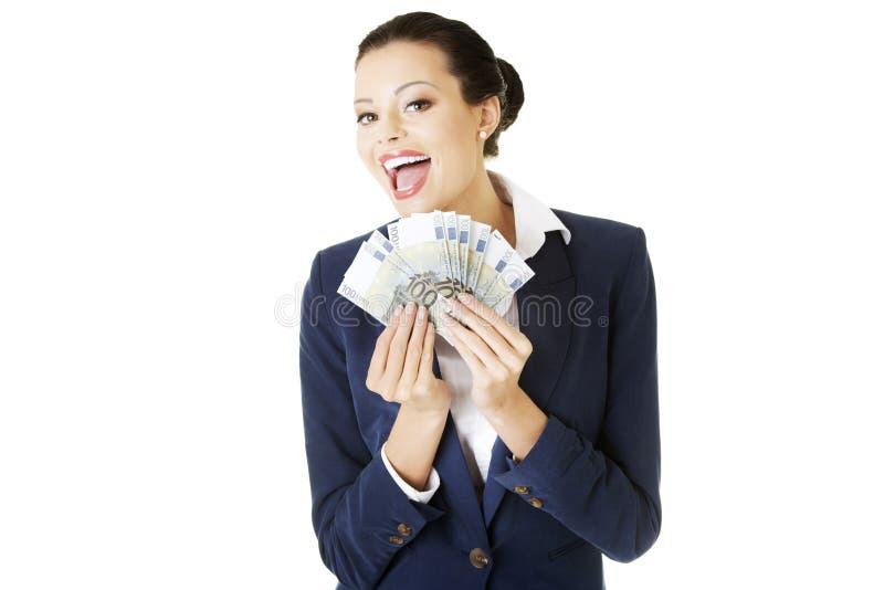 拿着欧元的愉快的女实业家 免版税库存图片