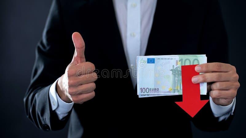 拿着欧洲钞票的财务专家,显示赞许和下来,落 免版税图库摄影