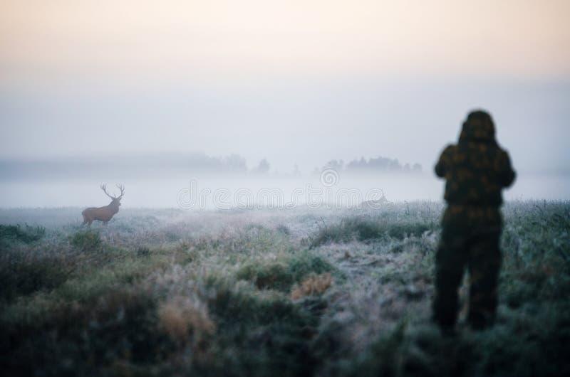 拿着步枪和瞄准马鹿,猎人的猎人photoshooting 免版税库存图片