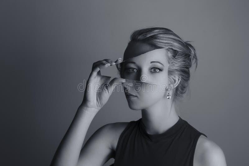 拿着残破的镜子的碎片妇女创造性的转换  免版税库存照片