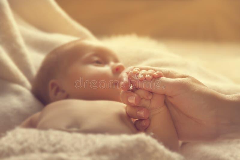 拿着母亲手、婴儿和父母的新出生的婴孩 图库摄影