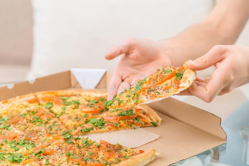 拿着比萨饼的饥饿的人 库存图片