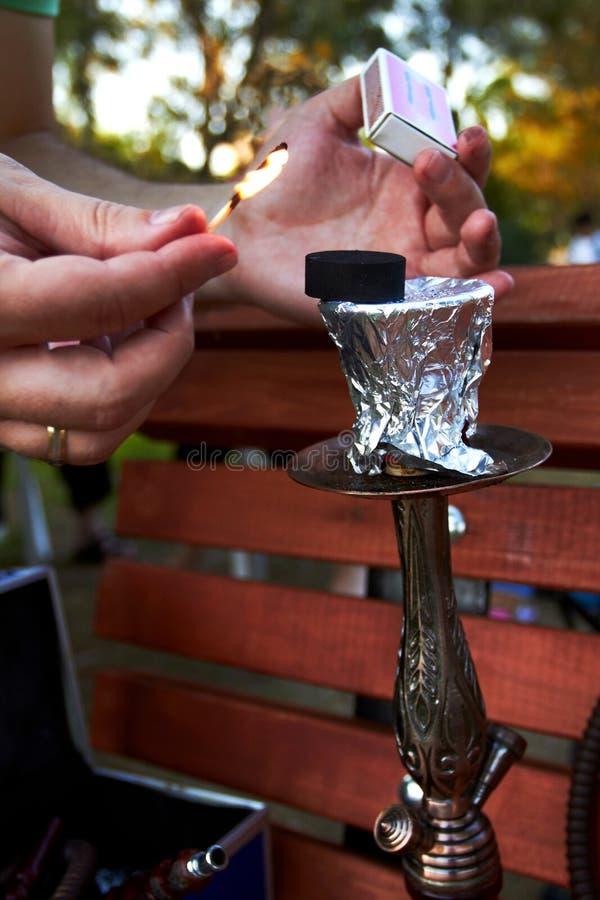 拿着比赛和灼烧的煤炭水烟筒的手在公园 免版税库存照片