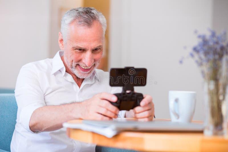 拿着比赛控制台的快乐的老人 免版税库存照片