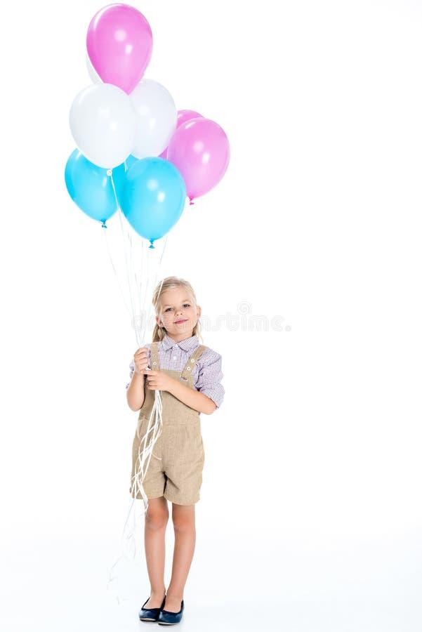 拿着气球和微笑对照相机的美丽的小女孩 库存照片