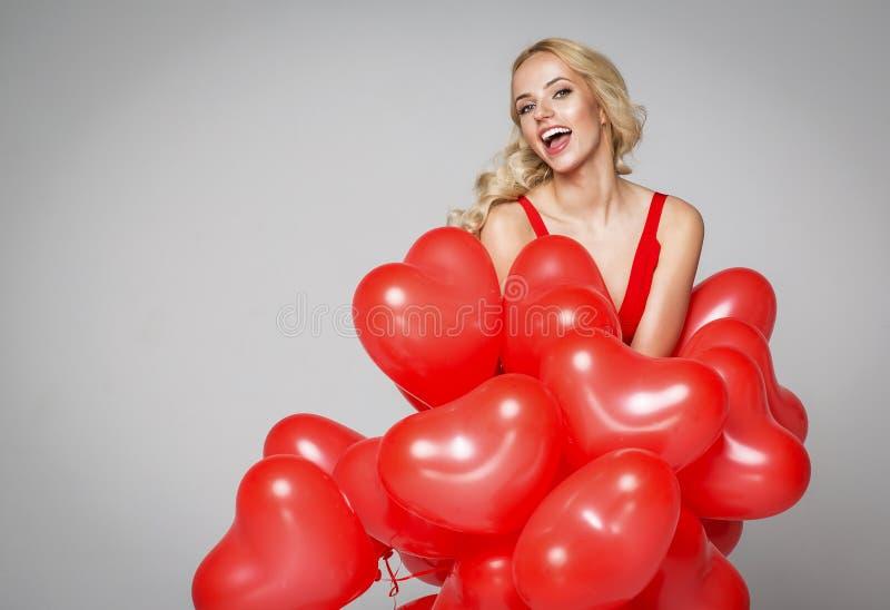 拿着气球心脏的美丽的微笑的白肤金发的妇女 r 免版税图库摄影