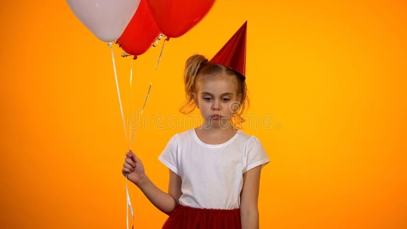 拿着气球的哀伤的青春期前的女孩,庆祝单独生日,有朋友 免版税库存图片