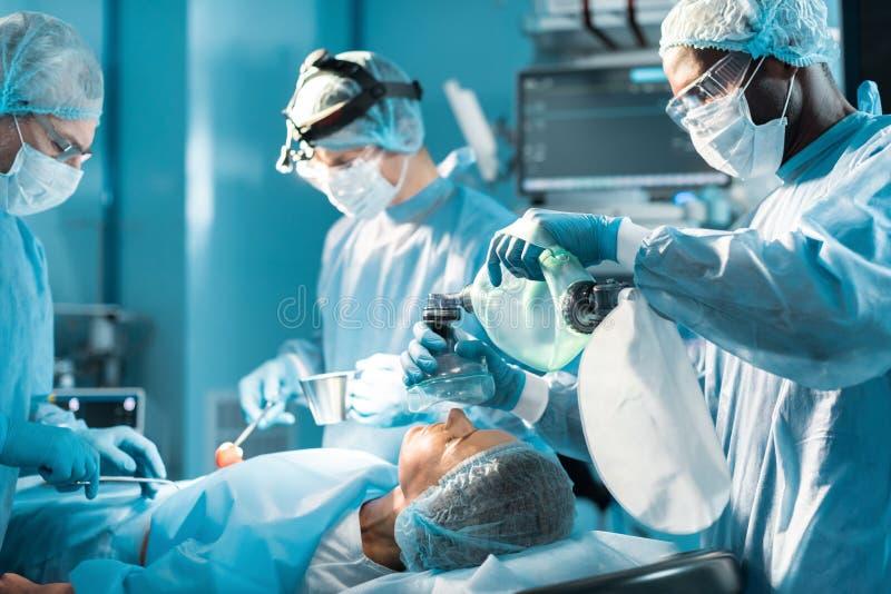 拿着氧气面罩的非裔美国人的麻醉师 免版税库存照片