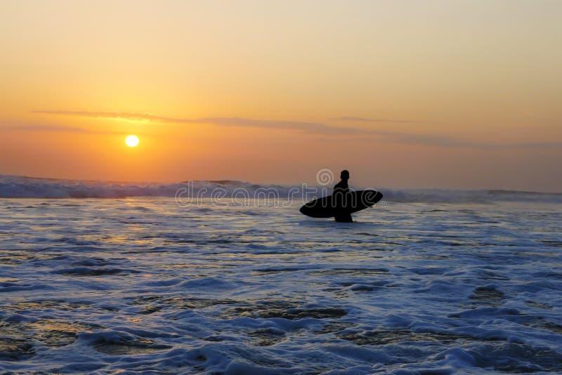 拿着水橇板的未知的匿名冲浪者剪影在冲浪在与惊人的美好的阳光的日落以后与橙色天空 库存照片