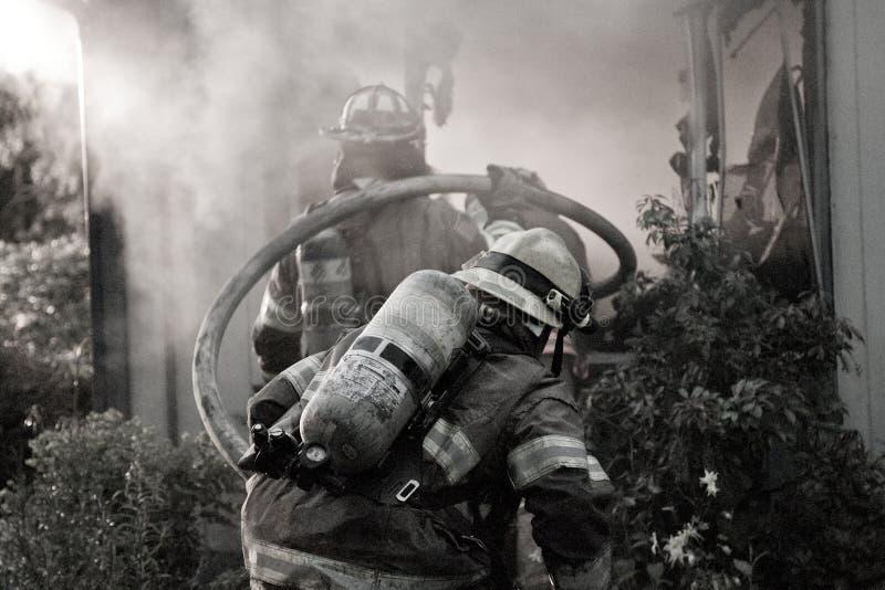 拿着水管的消防队员 免版税图库摄影