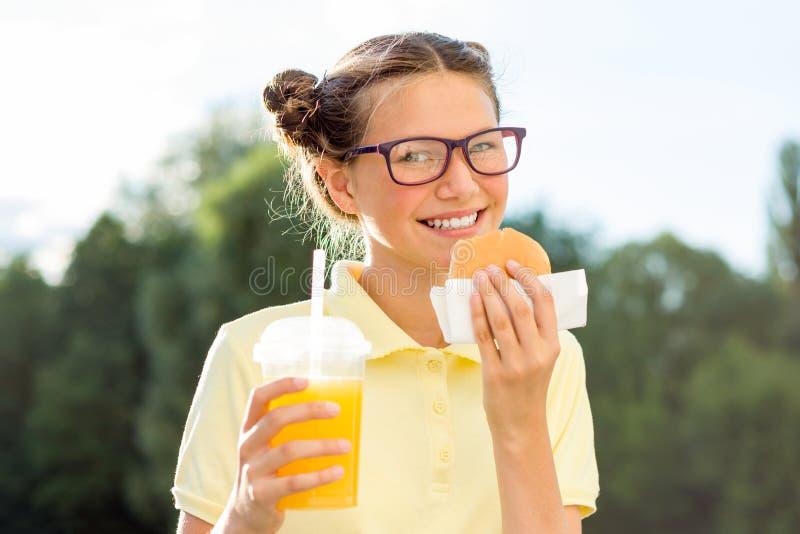 拿着汉堡包和橙汁的逗人喜爱的微笑的青少年的女孩室外 库存照片