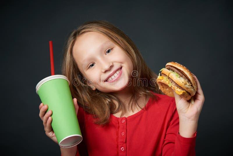 拿着汉堡包和纸杯的微笑的女孩特写镜头 图库摄影