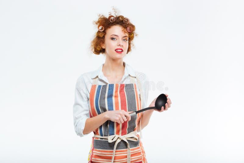 拿着汤杓子的围裙的主妇 库存照片