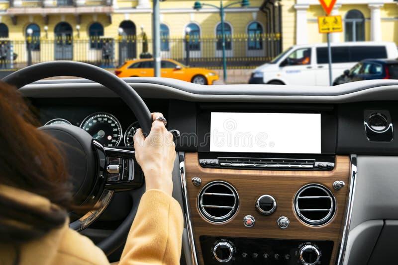 拿着汽车一辆现代汽车的方向盘的妇女手 在驾车的方向盘的手 驾驶在客舱里面的女孩一辆汽车 免版税库存图片