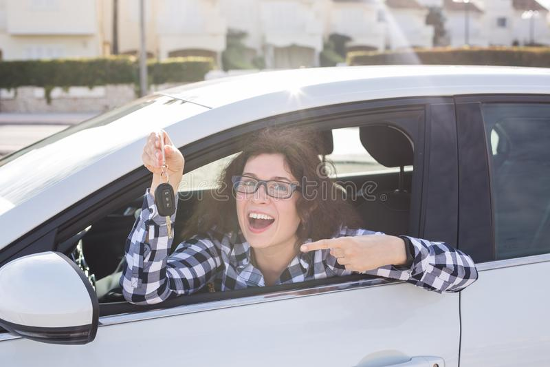 拿着汽车的妇女司机锁上在她新的汽车的选址 库存照片