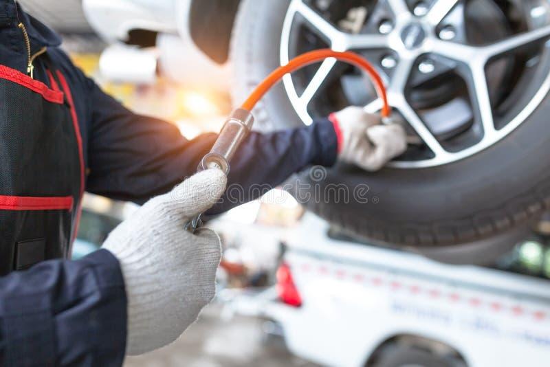 拿着汽车轮胎气压测量的手特写镜头压力表在自动汽车维修车间 免版税库存图片