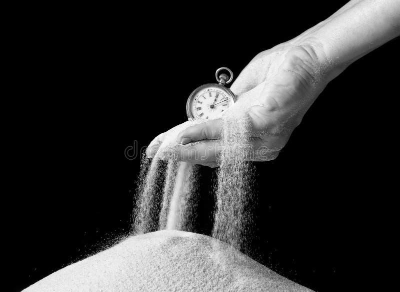 拿着沙子和时钟的手 库存图片