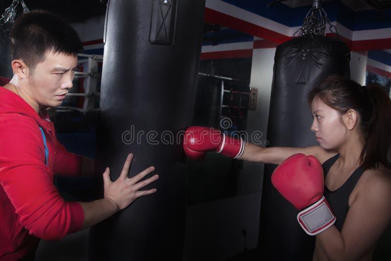 拿着沙袋和训练一个女学生的拳击长沙发 免版税图库摄影